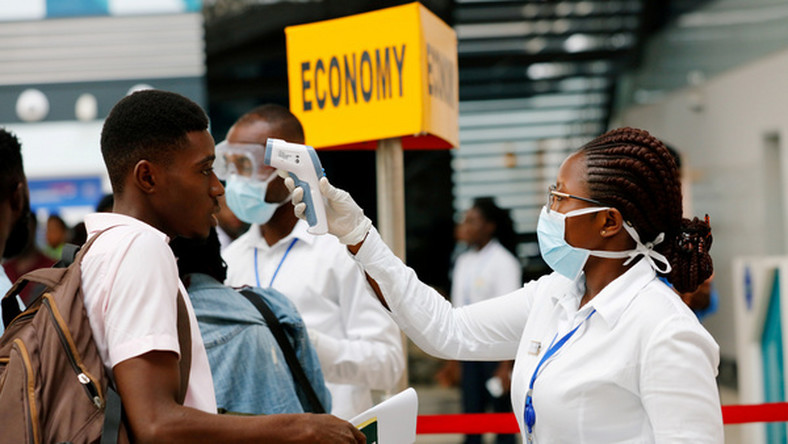 A health worker checks temperature of traveller as part of Coronavirus screening procedure at the Kotoka International Airport