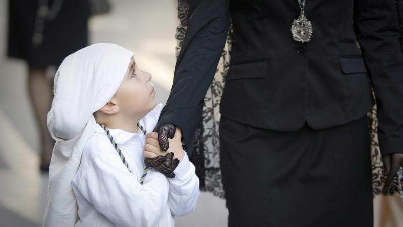 Ubrany w tradycyjny strój chłopiec idzie z matką na procesję z okazji Świętego Tygodnia organizowaną w Almerii na południu Hiszpanii; kwiecień 2012 roku