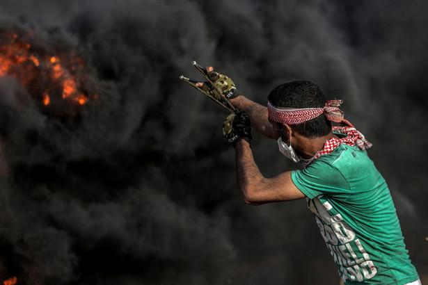 Protestujący celuje z procy w stronę granicy z Izraelem