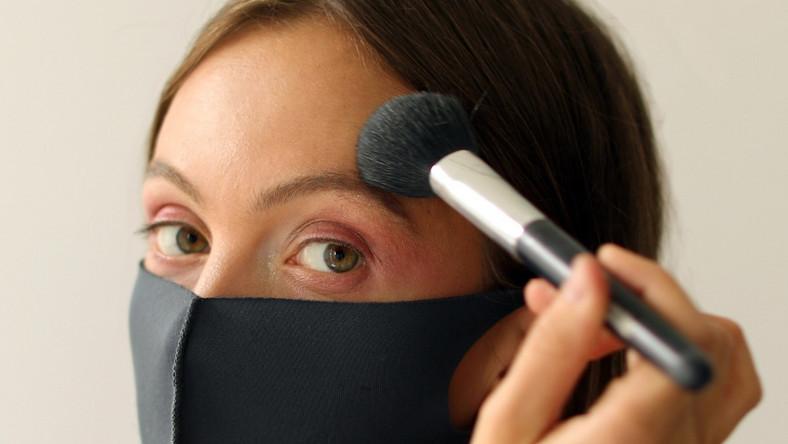 Kobieta w maseczce robi makijaż