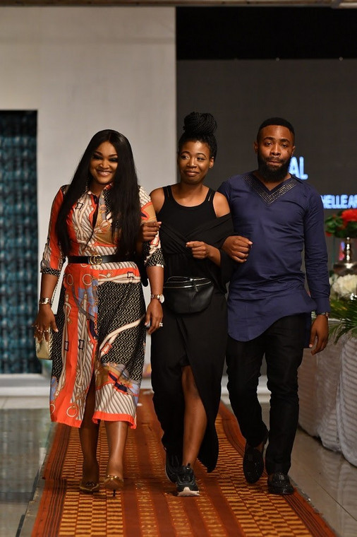 Mercy Aigbe and Woli Arole walking the runway with Michelle Arowoshola