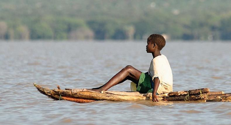 A boy floats on a locally made canoe across Lake Baringo. (eastafricanjunglesafaris.)