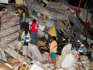 People stand on the debris of a building after an earthquake struck off the Pacific coast in Manta