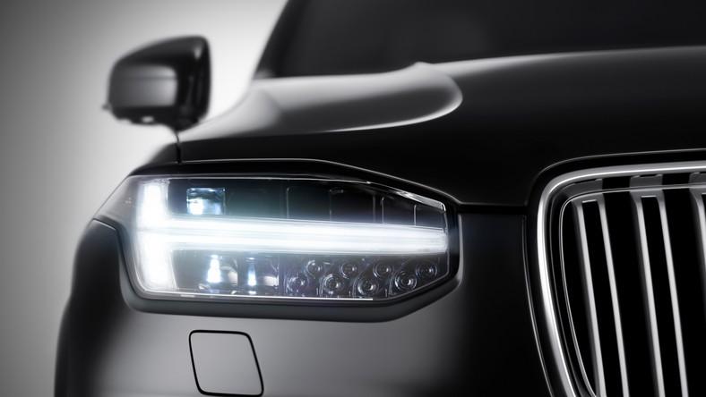 """Volvo po raz pierwszy pochwaliło się zdjęciem fragmentu nowego XC90. Na fotografii widać przedni reflektor z włączonym światłem do jazdy dziennej LED w kształcie ułożonej poziomo litery T. Zdaniem projektantów będzie to charakterystyczny element, który pozwoli na rozpoznanie auta, zaś samo T styliści nazwali """"młot Thora"""", ponieważ przypomina swoim zarysem oręż słynnego nordyckiego boga piorunów - Thora. Przy okazji Szwedzi ujawnili także kilka informacji o nowej modularnej płycie podłogowej, na której oparto nowe XC90 - Scalable Platform Architecture (SPA)."""