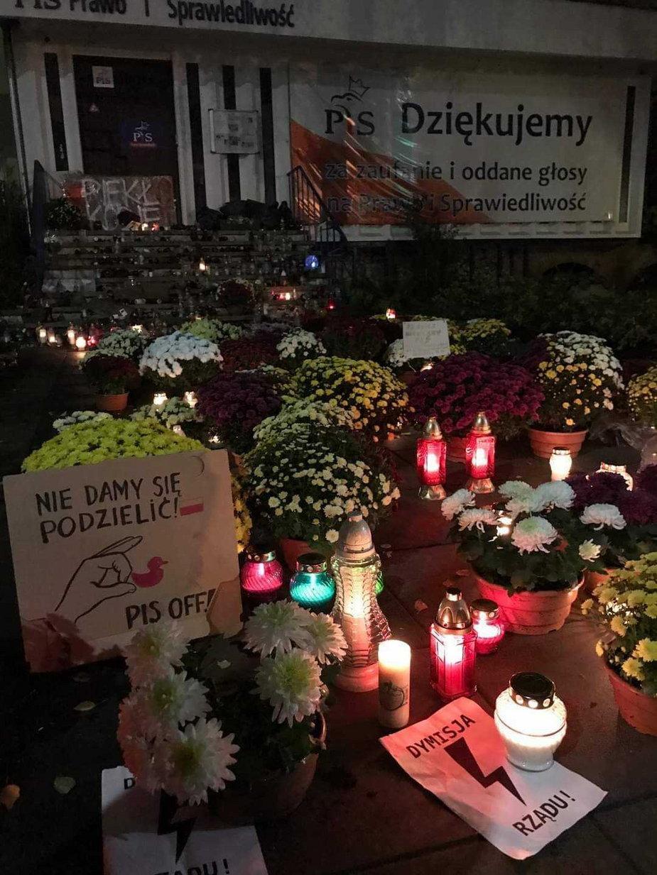 Chryzantemy i znicze przed siedzibą PiS w Szczecinie