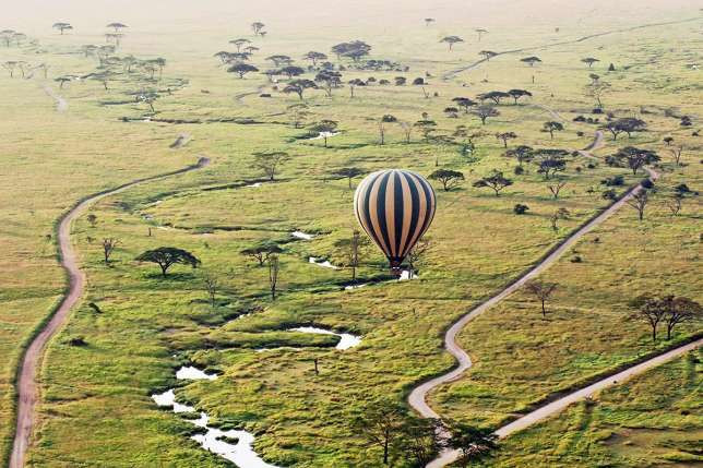 An hot air balloon flies over the famed Maasai Mara game reserve in Kenya. (Art of Safari)