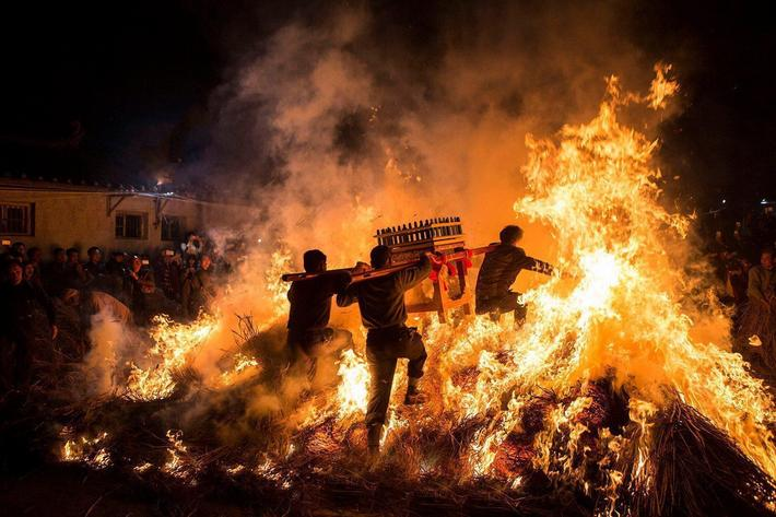 Men carrying a shrine jump over a bon fire, which means a wish for good luck during a traditional Ch