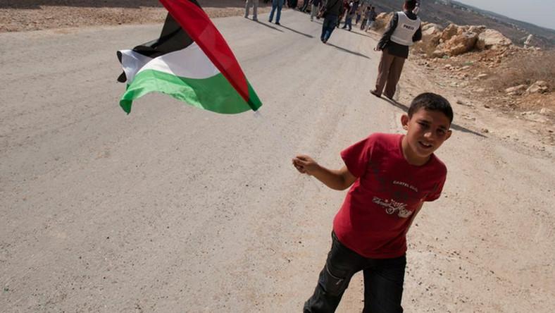 Chłopiec trzymający flagę Palestyny