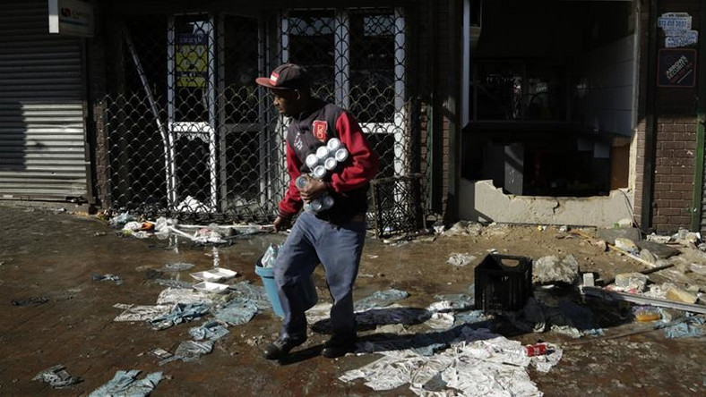 A looter makes off with goods from a store in Germiston, east of Johannesburg, South Africa [Themba Hadebe/The Associated Press]