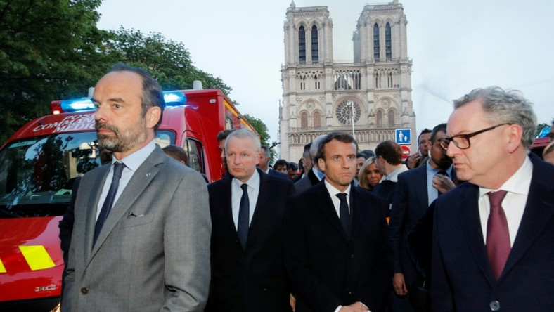 French Prime Minister Edouard Philippe (L), and French President Emmanuel Macron (3rd L) gather near the entrance of the Notre-Dame Cathedral in Paris, as flames engulf its roof