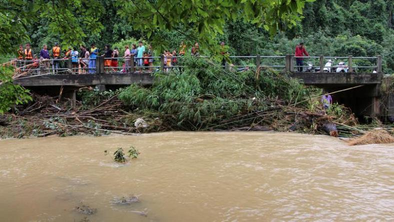 Onlookers and rescue workers stand on a bridge in a flooded area in Sichon District, Nakhon Si Thammarat province, Thailand December 4, 2016.