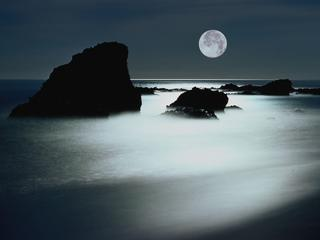 Full moon over rocky shoreline