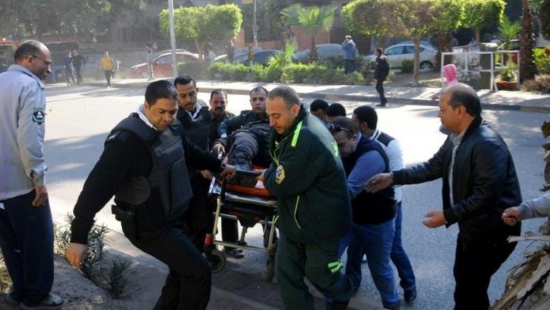 Egyptian emergency services carry a wounded victim at the site of a bomb attack next to a police checkpoint in Cairo on December 9, 2016