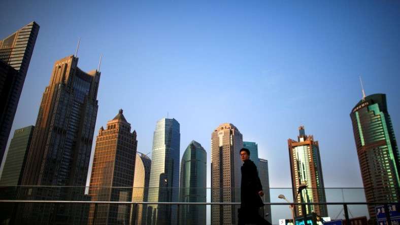 A man walks at the financial district of Pudong in Shanghai.