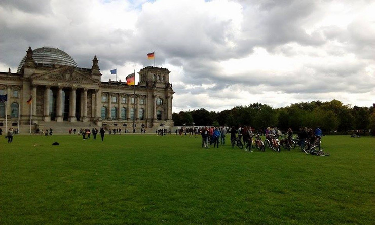 Turisti ispred Bundestaga planiraju obilazak grada iznajmljenim biciklima