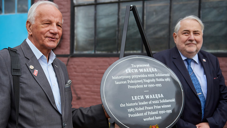 Działacze antykomunistyczni Jan Rulewski (L) i Tadeusz Syryjczyk (P) przy tablicy pamiątkowej odsłoniętej przed warsztatem, w którym pracował Lech Wałęsa