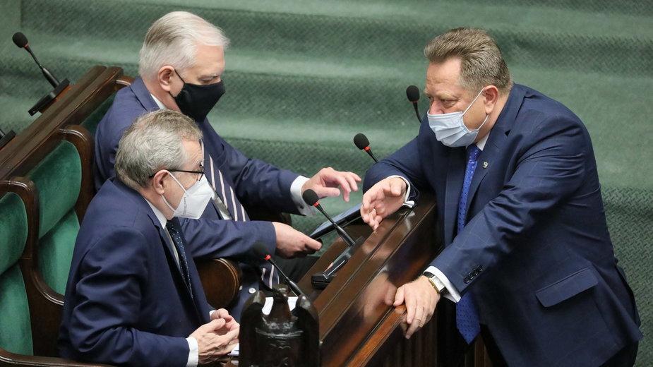 Jarosław Zieliński na sali sejmowej rozmawia z Jarosławem Gowinem i Piotrem Glińskim