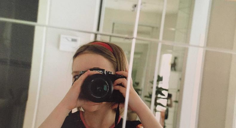 Finley Muratova, pictured here at age 10 taking a selfie with their father's camera.
