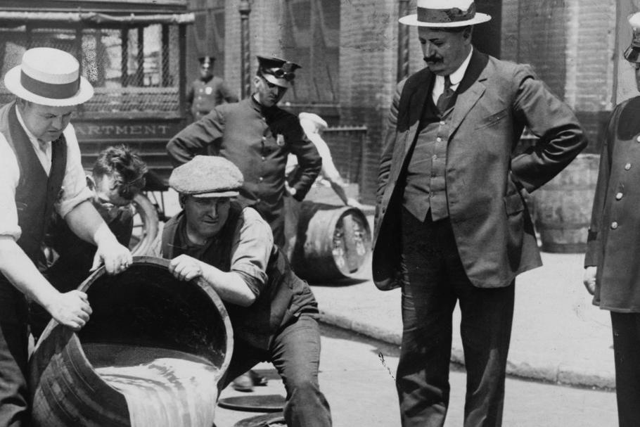Prohibition in the USA 1920-1933: A barrel of confiscated illegal beer being poured down a drain. Al