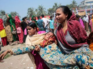 Women help a relative of a garment worker, who went missing in the Rana Plaza collapse, after she fa