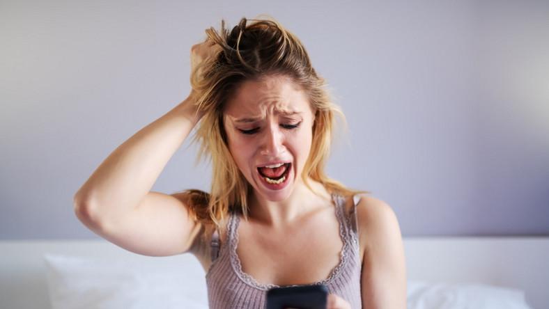 Kobieta odczytuje SMS i krzyczy w łóżku