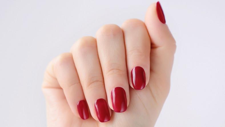 Dłoń z pomalowanymi na czerwona paznokciami