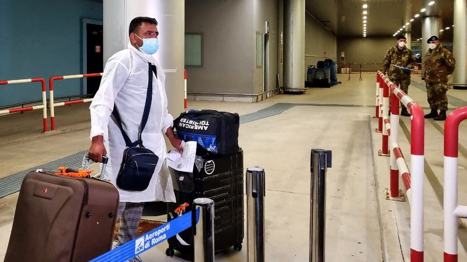 Pasażer lecący z Indii przybywa ze swoim bagażem na lotnisko Fiumicino International późno 28 kwietnia 2021 roku