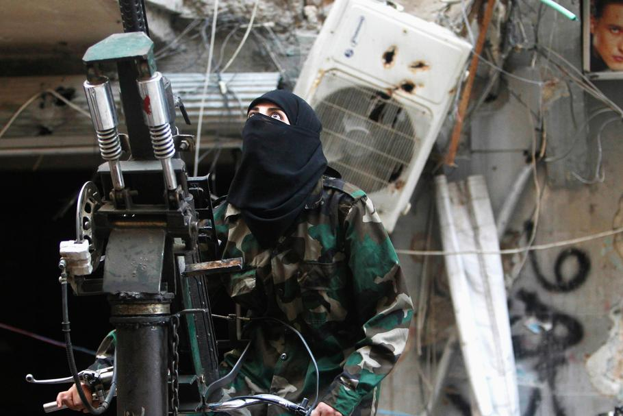 A female member of the Ahbab Al-Mustafa Battalion stands on a pick-up truck mounted with an anti-air
