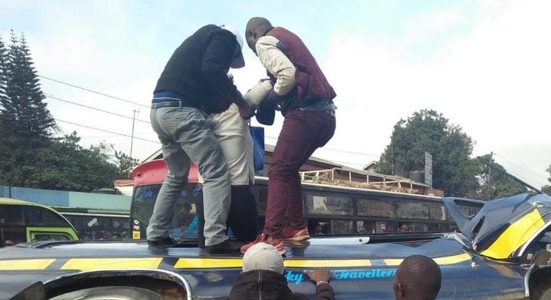 Members of the public assist passengers on 14-seater matatu that overturned at Ngara along Murang'a Road