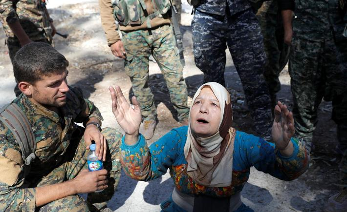 A civilian prays after she was rescued by fighters of Syrian Democratic Forces from the stadium afte