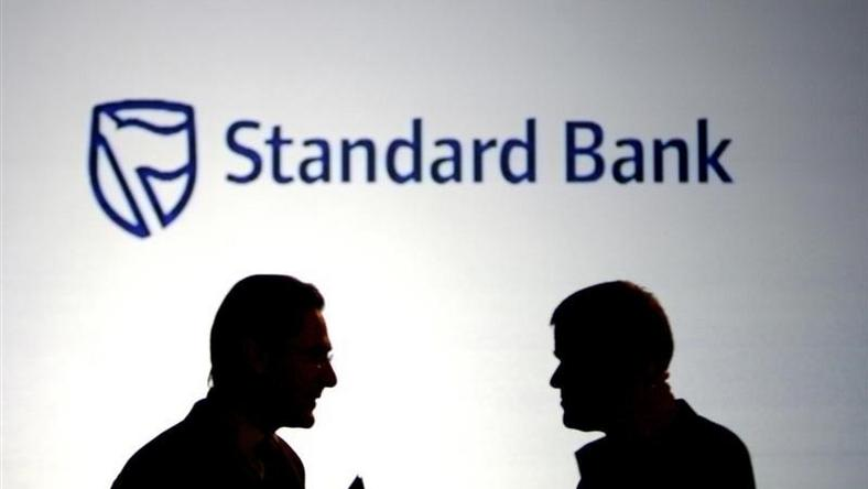 Businessmen chat in front of a Standard Bank logo in Sandton outside Johannesburg,  file.   REUTERS/Siphiwe Sibeko