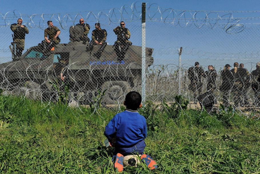 A boy sits on his ball next to a border fence on the Greek side of the border, as Macedonian police