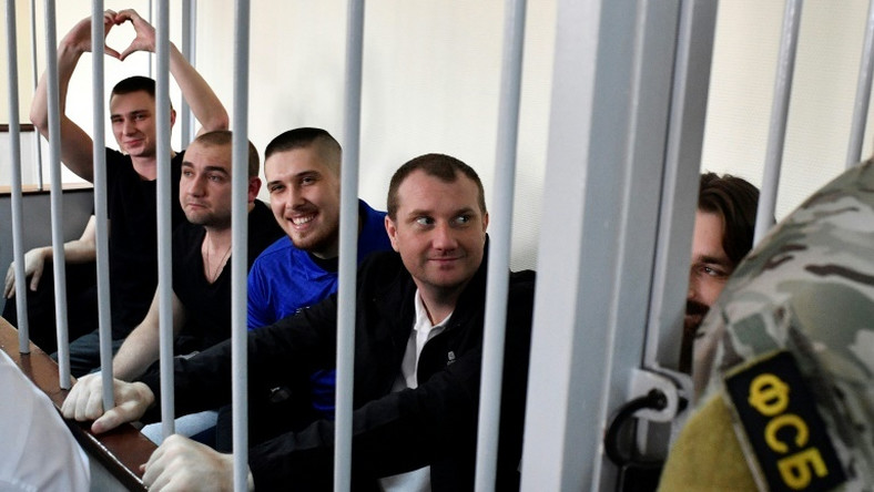 In the cramped courtroom, the sailors, who have described themselves as 'prisoners of war', were held in a metal-barred cage reserved for defendants