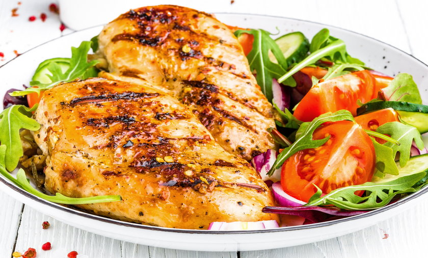 Grilled chicken breast. Fried chicken fillet and fresh vegetable salad of tomatoes, cucumbers and ar