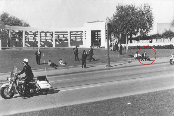 Čovek sa kišobranom slikan na travi nakon ubistva Kenedija