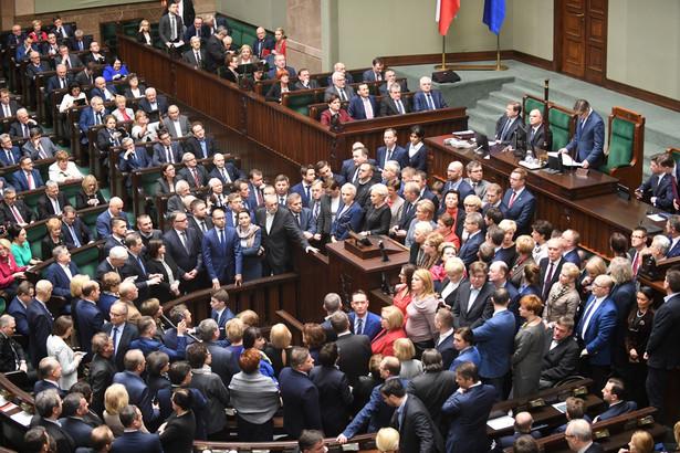 Część posłów opuściła salę plenarną. Wokół mównicy sejmowej pozostaje grupa posłów PO.