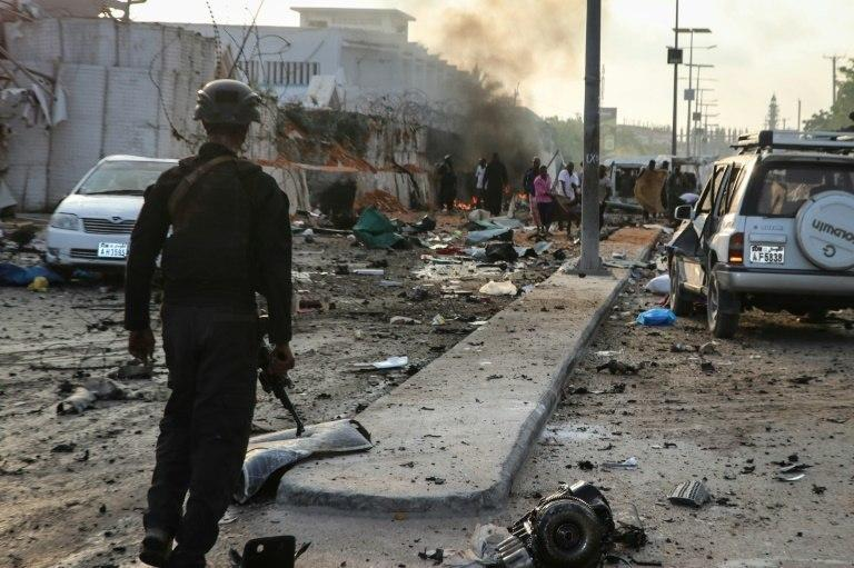 A Somali security officer looks on at the aftermath of two car bomb blasts, which occurred within moments of each other. A third blast was caused by a suicide bomber who detonated an explosives vest