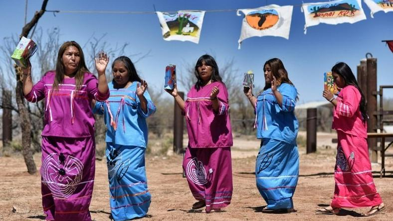 Indigenous people from the Tohono O'odham ethnic group dance and sing to protest against US President Donald Trump's intention to build a new wall in the border between Mexico and United States, in the Altar desert, northern Mexico