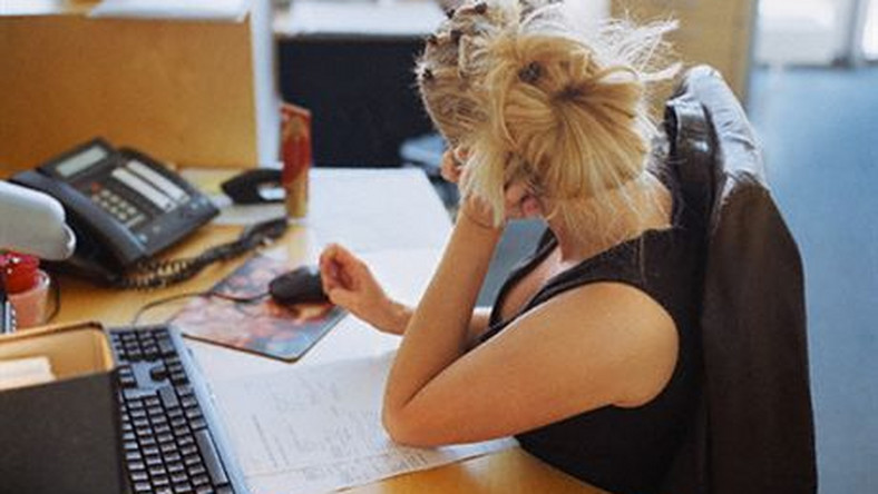 Bored Woman Sitting at Her Desk --- Image by © Helen King/Corbis