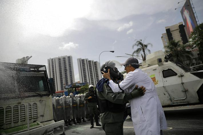 A demonstrator talks with a member of the Venezuelan National Guard during riots at a rally called b