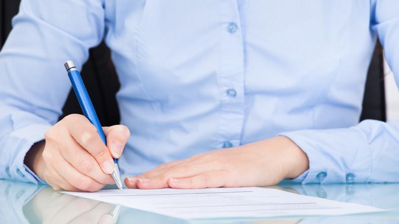 Urzędniczka podpisuje dokument