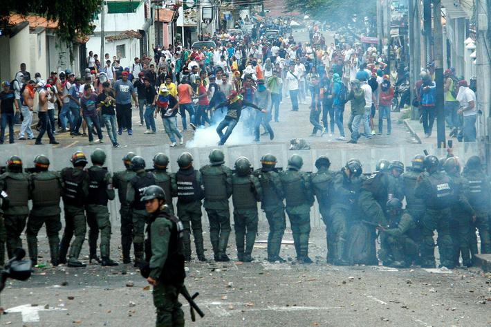 Demonstrators clash with members of Venezuelan National Guard during a rally demanding a referendum