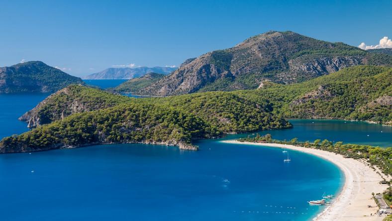 """Ölüdeniz nazywa się często błękitną laguną, jednak w rzeczywistości nazwa ta oznacza zupełnie co innego. Można ją przetłumaczyć jako """"martwe morze"""", co odnosi się do tego, że wody w tej części Riwiery Tureckiej pozostają zawsze spokojne. Miejsce to położone jest w zasadzie na granicy pomiędzy Morzem Śródziemnym i Morzem Egejskim. Słynie z pięknych krajobrazów. Fotografowie udają się tu nie bez powodu - tak lazurowych wód nie znajdzie się nawet na francuskim wybrzeżu! Jednocześnie tutejsza plaża uznawana jest za jedną z kilku najpiękniejszych na całym świecie. Mogłoby się wydawać, iż taka rekomendacja sprawia, że co roku ściągają tu tłumy turystów, a - co za tym idzie - wybrzeże staje się coraz zdewastowane. Na szczęście przypadek ten nie dotknął Ölüdeniz. Tutejsza plaża otrzymała odznaczenie Błękitnej Flagi, można być więc pewnym, że jest nie tylko pięknie, ale również czysto i bezpiecznie."""