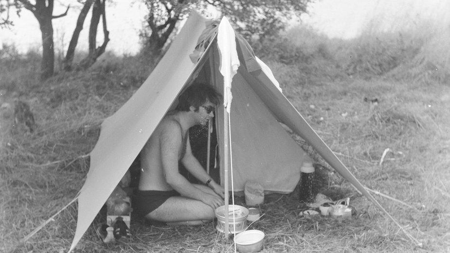 """Marek Rutowski na Mazurach w namiocie przy kuchence turystycznej """"Wisła"""", 1973 r."""