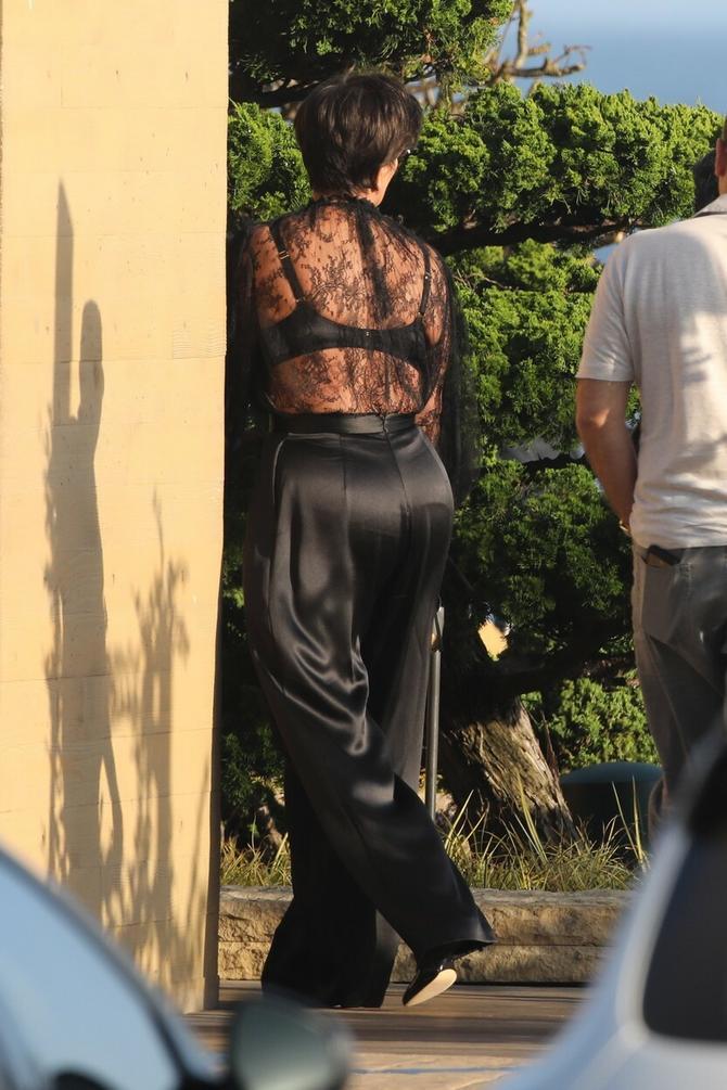 Čipkanu bluzu uparila je sa crnim, satenskim pantalonama