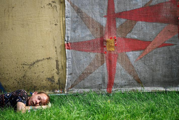 A reveller sleeps at Worthy Farm in Somerset during the Glastonbury Festival