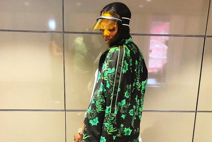 Tiwa Savage wearing her Nike Super Eagles tracksuit with a Dior visor and white sneakers