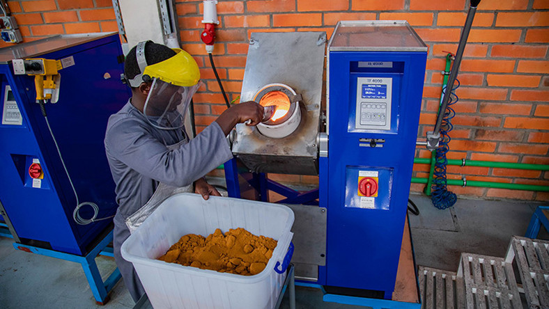 A worker at Aldango Gold Refinery puts gold powder into a high temperature heating device to melt.