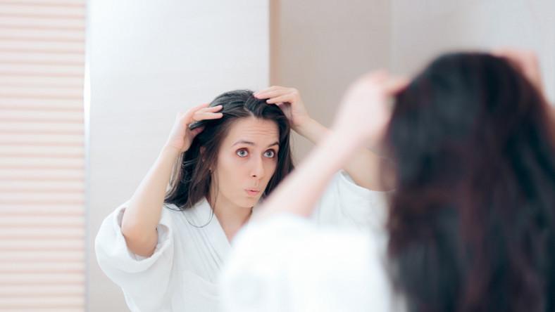 Kobieta ogląda swoje włosy w lustrze