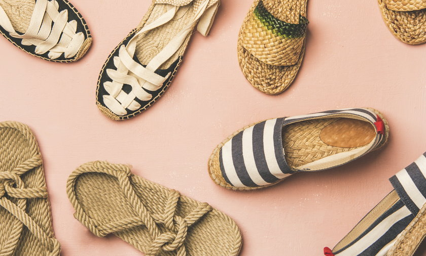 Trendy summer shoes over pastel pink background, top view